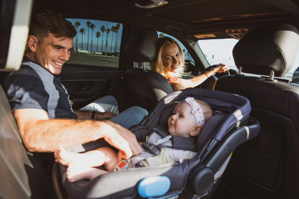Travel with baby in the car, young father fixing the baby car seat